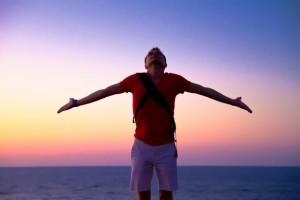 hombre encima de una montaña al atardecer con los brazos abiertos